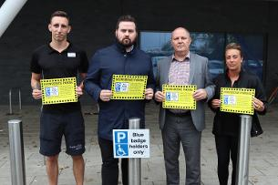 Decorative image showing a photo of Councillor Callaghan with Basildon Sporting Village staff displaying new disabled parking signs
