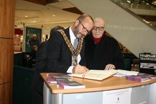 Mayor of Basildon, Cllr David Dadds, signs the Book of Remembrance alongside Holocaust survivor Leslie Kleinman